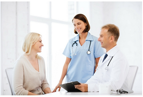 A female and male healthcare provider talking to a female patient