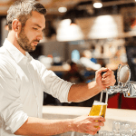 A Bartender filling a cup up with beer