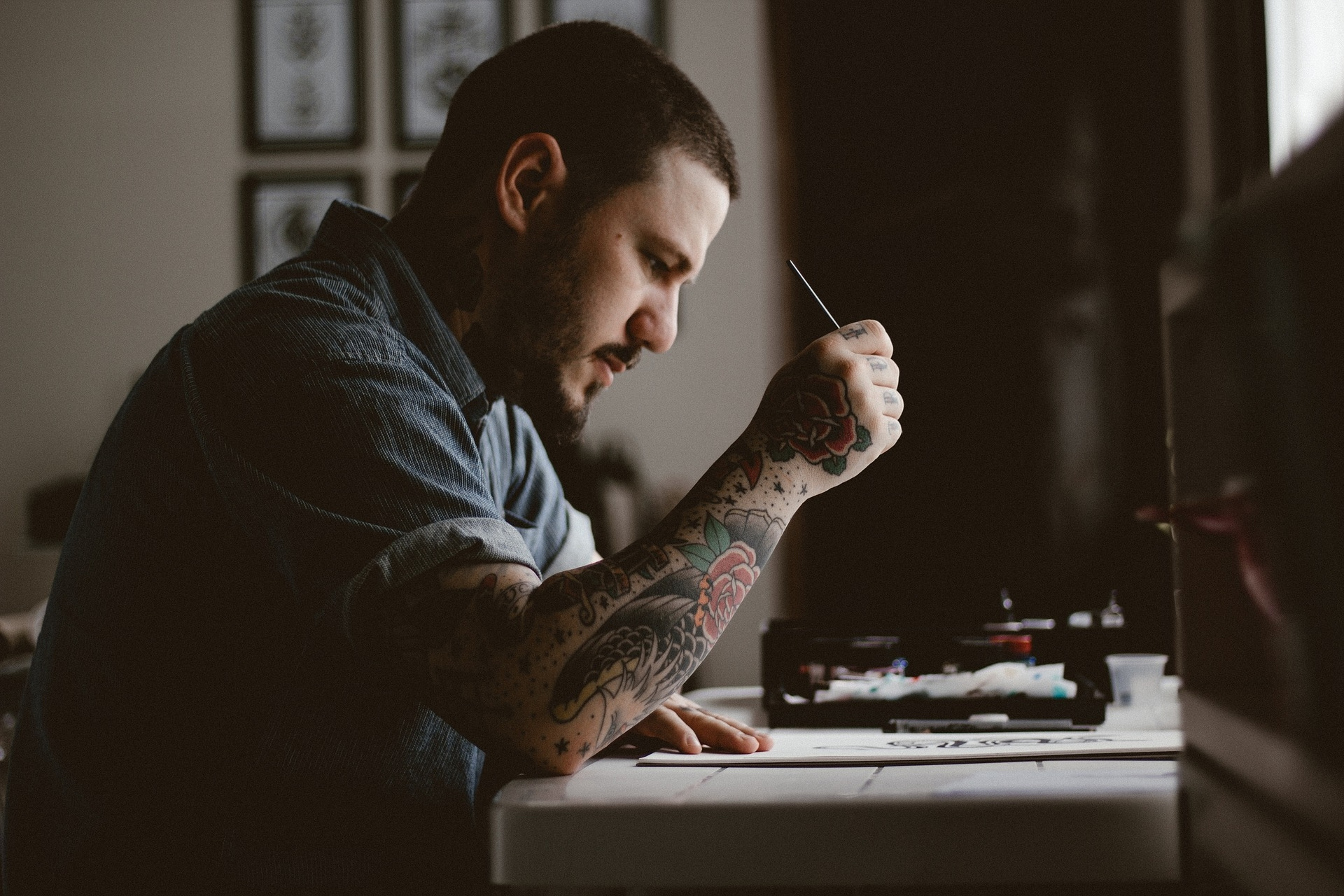 Man with arm tattoo writing