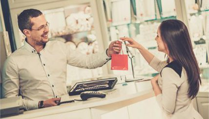 Female retail employee handing a bag to a male customer