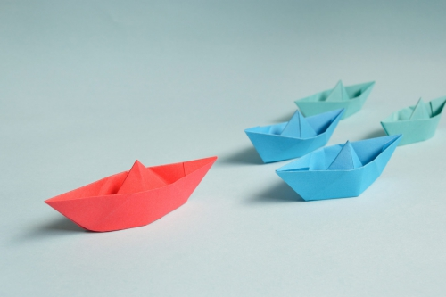 One red paper boat, two blue paper boats, two teal paper boats