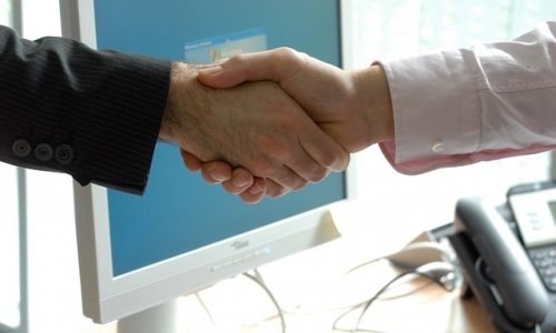 Two men shaking hands in front of a computer monitor and desk phone